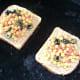 Sandwich filling is spread on bread on grill pan