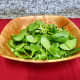 Rinse the baby spinach and add it to the salad bowl.