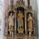 A carved altar piece depicting St. Joseph and the Christ Child, flanked by St.Edith and Rupert Mayer, S.J.