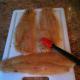 Basting the flounder fillet with teriyaki sauce.