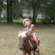 My granddaughter with her pony and riding helmet.