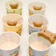 Gently place a dog biscuit into the center of each cup's mixture.