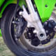Location of the brake caliper; on the rear side of the front wheel.