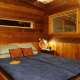 A bedroom space can be simultaneously cozy, enclosed within warm, antique wood, and open with windows to the outside.