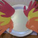 Glue or tape 3 hands to each side of the large plate to create the feathers.