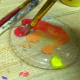 Mixing red and yellow in the paint tray.