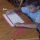 Glue red stripes on white construction paper.