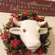Wall Cow with a plastic wreath around its neck