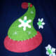 The elf hat is a felt Christmas tree ornament hot glued to an old cotton sweater vest.