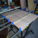 Clamping the doweled panel together (keeping it flat) until the glue dries.