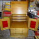 Completed sewing machine cabinet in workshop with doors and lid open
