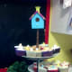 Painted birdhouse surrounded by bird nest cupcakes.