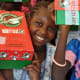 A girl holding up her shoebox in Senegal.