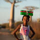 A girl balancing her shoebox on her head in Madagascar.