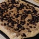 The rolled out dough topped with raisins and walnuts