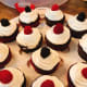Moist chocolate cupcakes with vanilla frosting topped with fresh red raspberries and blackberries