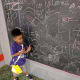 Juju shows off his doodle at the chalkboard.