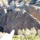 """From the upper trail, note where my finger points down. Those little holes in the cliffs are big enough for rock climbers to sit inside. The faint line of holes going up on the right is their ascension """"trail."""""""