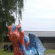 Norvica Serafina, meaning 'Fiery One', by Norwich School, standing in Cathedral Close.  The scales were created using finger prints of the staff & pupils of the school.