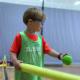 Boy in green hits ball off air tee