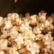 Slowly add popcorn kernels, stirring.