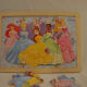 12-piece Disney Princesses interlocking puzzle, with identical background.