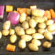 Prepared vegetables are oiled and seasoned in the base of the roasting tray