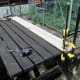 Cutting wood width with circular saw with parallel guide and clamps to secure to patio bench.