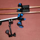 Shoulder Rig with camera plate on top of parallel supports, hand grips below, and articulating magic arm and support clamp.