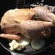 Using REAL butter, NOT margarine, coat the entire outside of the chicken with a nice layer of butter.  Put a glop of butter in the pan, you'll use that for basting.  Make sure you salt and pepper the outside to your liking.