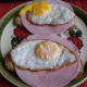 Fried eggs are added to the slices of Graubrot with ham.
