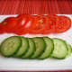 Slices of tomatoes and cucumber for topping.