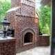 brick fireplace appearing massive in scale complete with brick pedestals holding lanterns