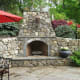 rustic stone outdoor fireplace with raised hearth and round grey and tan stones