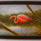 A framed painting of a flamingo in the wetlands.