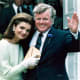 Jackie Kennedy wearing gloves standing next to Ted Kennedy  waving