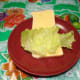 White bread spread with margarine or butter and lettuce on top.