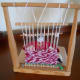 View through the loom at a woman weaving