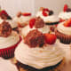 Chocolate cupcakes with vanilla frosting, freshly sliced strawberries, and hazelnut Ferrero Rocher chocolate