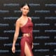 Megan Fox in a revealing dress with a hip high slit up the side wearing platform high heels