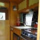 Interior of our Vintage camper with her new boomerang curtains, cutting board fitted to sink & mirror.