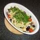 Fusilli pasta and parsley are added to the roasted vegetables