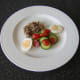 Salad and egg are plated with a thick slice of jellied ox tongue