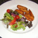 Sweet potato fries are plated with salad bed for tuna