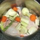 Chopped and prepared vegetables are added to stock pot with duck legs