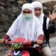 An Indonesian woman in Banda Aceh, wearing her doa guan.