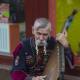 A Ukrainian wearing traditional garb, playing the bandura (a Ukrainian, plucked string, folk instrument)