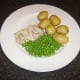 Poached chicken leg meat with new potatoes and peas