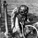 Sponge diver on edge of boat with sponge - Tarpon Springs