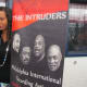 A young lady poses with the banner for The Intruders singing group.
